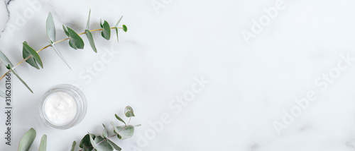 Natural organic cream jar with eucalyptus leaves on marble background. Flat lay, top view, copy space. Natural organic product, beauty and spa concept