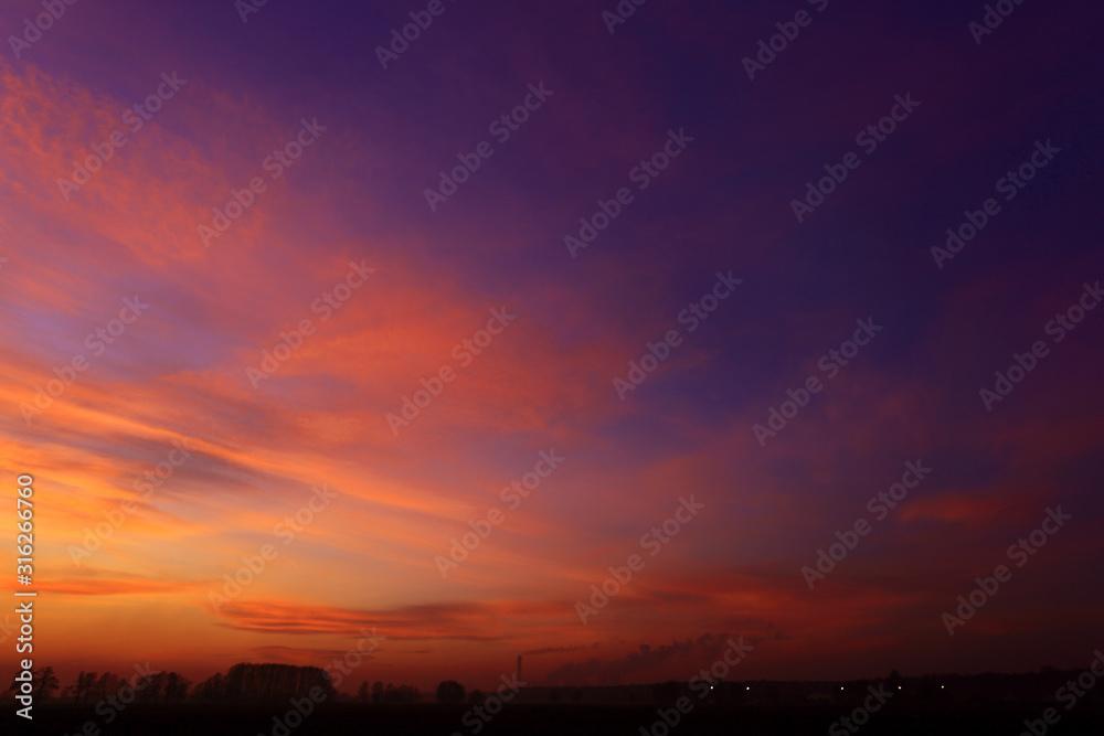 Złoty, pastelowy zachód słońca nad polami, obszry wiejskie.