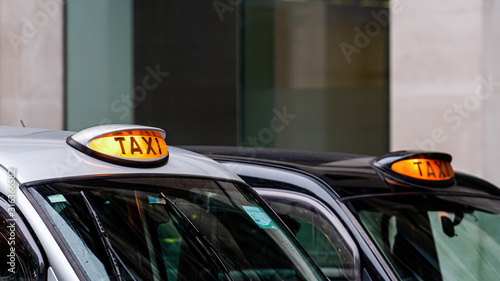 Fotografiet A british london black taxi cab sign with defocused  background