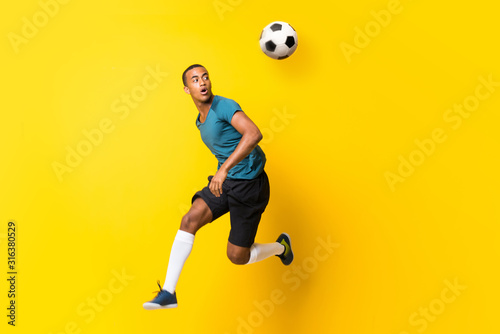 Carta da parati Afro American football player man over isolated yellow background