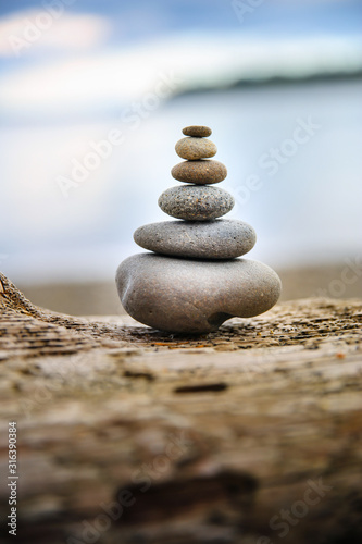 Leinwand Poster Cairn stone stack smooth stones at beach