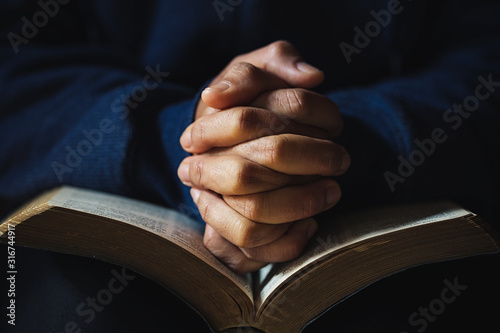 Hands folded in prayer on a Holy Bible in church concept for faith Fototapeta