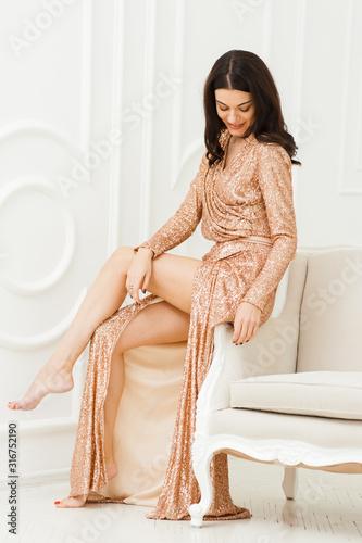 Canvastavla Fashionable woman in evening dress on white sofa