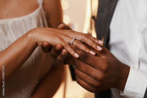 Afro guy putting ring on his girlfriend finger Fototapeta