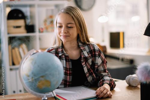 Valokuvatapetti Beautiful girl learning geography at home