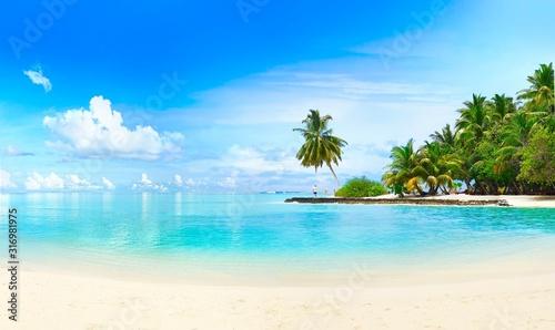 Piękna plaża z białym piaskiem, turkusowym oceanem, zielonymi palmami i niebieskim niebem z chmurami w słoneczny dzień. Letni tropikalny krajobraz, widok panoramiczny.