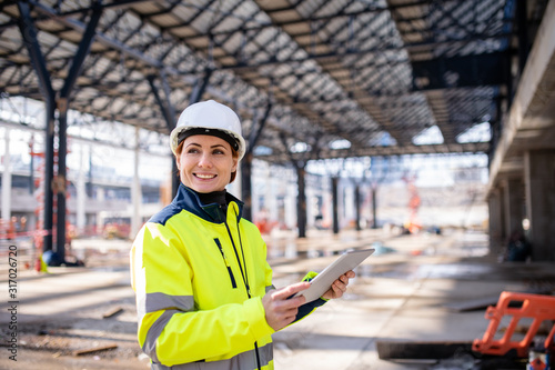 Fotografija A woman engineer with tablet standing on construction site, working