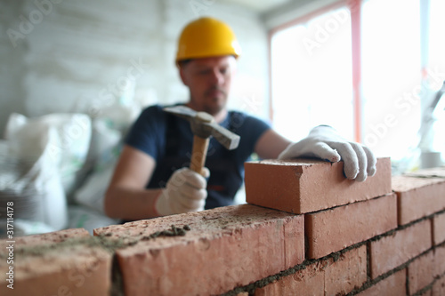 Fotografija Portrait of skilled man constructing big concrete wall and using special hammer to properly fulfill task to gently lay bricks on unfinished structure