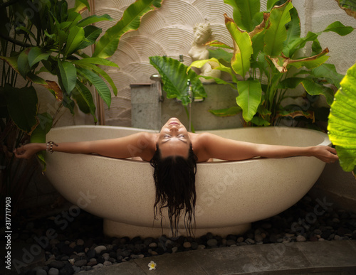 Leinwand Poster Woman relaxing in outdoor bath with tropical leaves at Bali