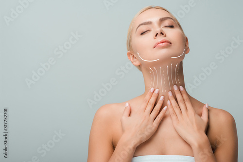 Fototapeta beautiful woman touching neck with lifting marks isolated on grey