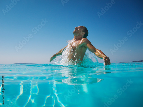 Athletic man emerging with a splash from rippling blue water Fototapet