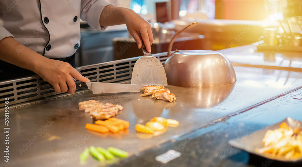 Japanese chef cooking meat in teppanyaki restaurant <span>plik: #318193166 | autor: Piman Khrutmuang</span>