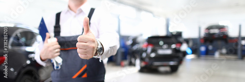 Fototapeta Focus on hand of happy engineer man showing thumb up and standing in modern car maintenance garage with automobiles