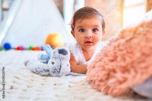 Fotografia Beautiful infant happy at kindergarten around colorful toys lying on blacket