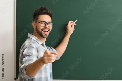 Fotografia Male teacher writing on blackboard in classroom