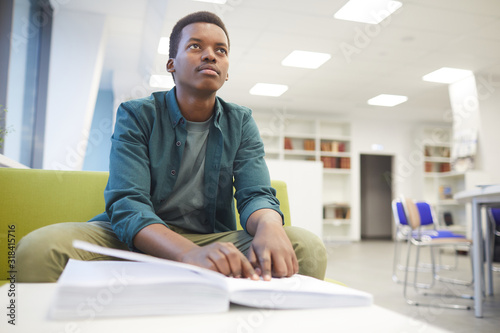 Fotografie, Tablou Portrait of young African-American man reading braille while studying in school
