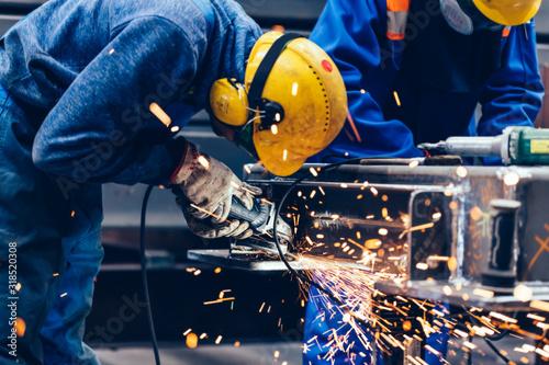 Obraz na plátne Worker grinding in a workshop. Heavy industry factory