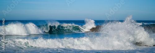 Fotografia, Obraz Large ocean waves crash against coastal stones on sunny day on European coast