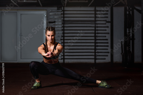 Fotografia Young beautiful muscular attractive fit girl stretch her hand and body muscles a