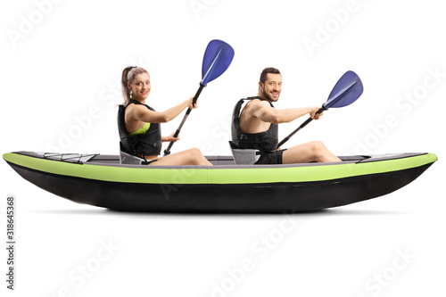 Fotografia Profile shot of a young man and woman with safety vest paddling in a canoe