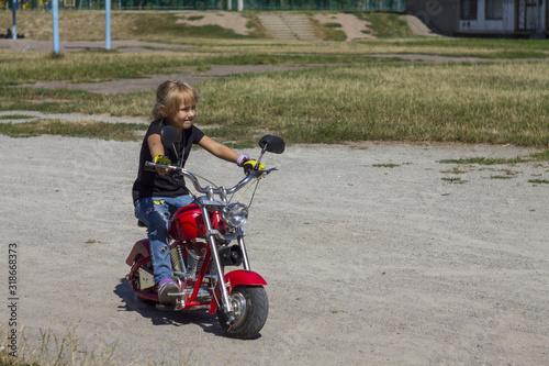 Fotografering little girl child rides a children's red cool minimoto electric bike chopper mot