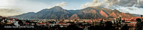 PANORAMIC SHOT OF TOWN BY MOUNTAINS AGAINST SKY