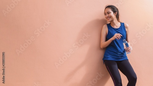 Fotografie, Obraz Asian beautiful women holding water bottle after play yoga and exercise on orange wall background with copy space