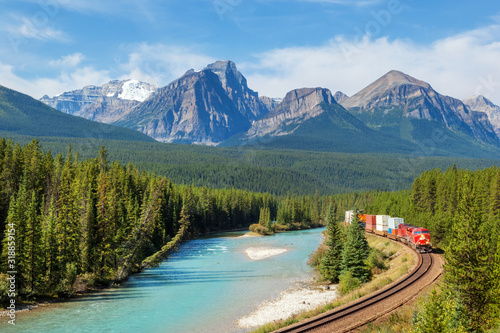 Wallpaper Mural Freight train moving along Bow river in Rocky Mountains range, Canada