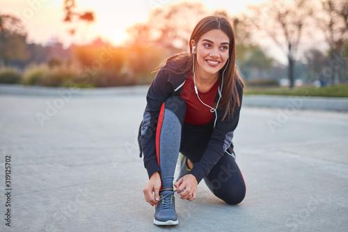 Young modern woman tying running shoes in urban park. Fototapeta