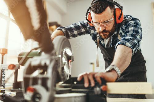 Billede på lærred young male carpenter working in  workshop