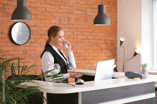 Fototapeta Young female receptionist talking by telephone at desk in hotel