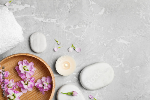 Flat lay composition with spa stones on light grey marble table, space for text