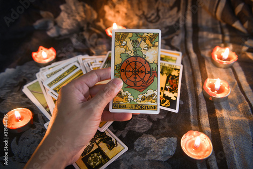 Fotografia Hand holding tarot card with candlelight on the darkness background for Astrolog