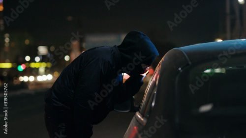 Canvas Print Robber man shines a flashlight in a car stealing at night crime male thief illeg