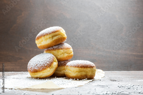 Close-up of donuts (Berlin pancakes) dusted with powdered sugar served on a rust Fototapet