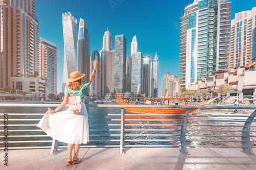 Obraz na plátně Cheerful asian traveler girl walking on a promenade in Dubai Marina district