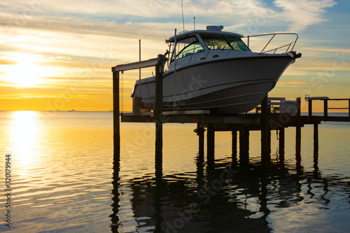Tablou Canvas Expensive fishing boat on electric motorized dock vessel lift during sunrise with colorful sky