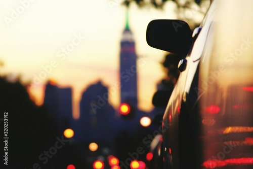 Wallpaper Mural Cropped Image Of Car On Street With Empire State Building In Background