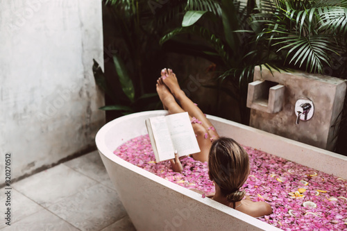 Photographie Woman reading book while relaxing in bath tub with flower petals