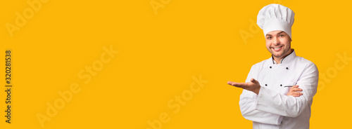 Tableau sur Toile Cook Man Gesturing Showing Something Standing Over Yellow Background, Panorama