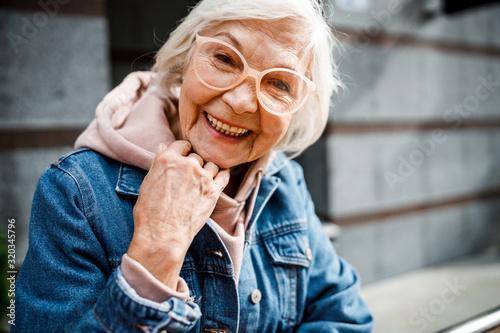 Obraz na plátne Smiling aged woman in jeans jacket stock photo