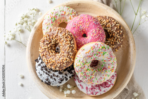 Homemade donuts with various decoration on white plate Fototapete