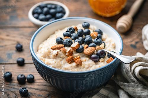 Billede på lærred Oatmeal porridge with blueberries, almonds in bowl on wooden table background