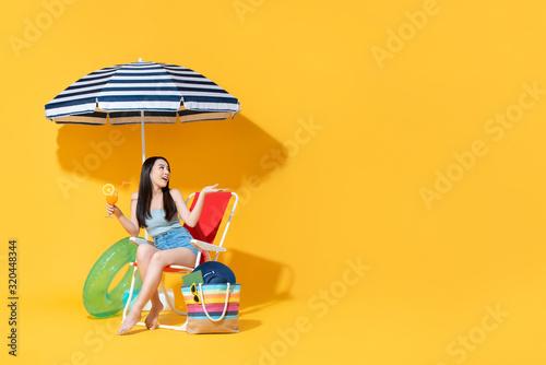 Fototapeta Surprised beautiful Asian woman sitting on beach chair