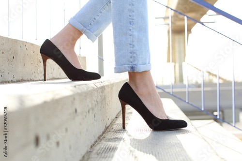 Fotografie, Obraz Profile of woman legs wearing high heels walking down stairs