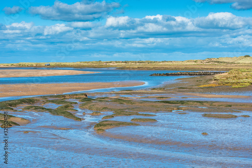 Fotografia Views of mudflats at low tide from Norfolk Coast path National Trail near Burnham Overy Staithe, Scolt Head Island to rear, East Anglia, England, UK