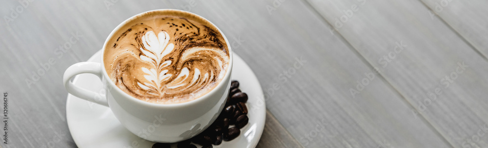 Fresh brewed coffee with fern pattern latte art in white cup