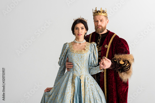 Fototapeta handsome king hugging queen with crown isolated on grey
