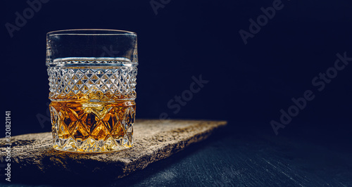 Canvas Print glass of whiskey with ice on a wooden table surrounded by smoke