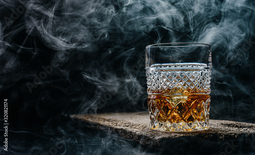 Photo glass of whiskey with ice on a wooden table surrounded by smoke